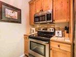 The kitchen is complete with stainless steel appliances including refrigerator, stove, microwave, dishwasher and other...