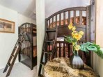 The loft bedroom has two sets of bunk beds and a large dresser.