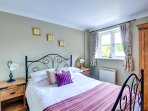 A comfortable double bedroom with co-ordinated soft furnishings