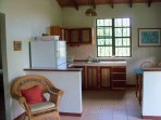 the kitchen with full sized fridge and 4 burner stove with oven