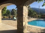 View from the veranda over the pool and terrace with the mountains in the distance