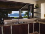 The fully-equipped kitchen has a view of the patio and Herradura Bay