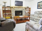 Spacious, cozy living room with reclining furniture, new carpet, internet, and gas fireplace.