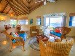 Open plan living room with ocean and garden views