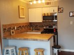 Electric full size stove, microwave, prep area with cabinet space (pots, pans, utensils, bowels, etc