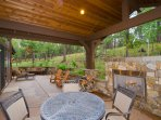 Rear covered patio with fireplace, built-in BBQ, dining table and seating areas.