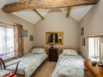 Twin bedroom with original beam and exposed stonework