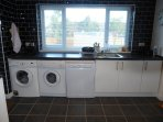 The wet end with sink, dishwasher, washing machine and tumble dryer