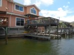 The back side to unit, with high deck, fish cleaner, swim ladder, boat lift/sling and dock,