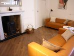The spacious living room has 2 comfy sofas and a functioning wood-burning stove.  + TV & DVD player