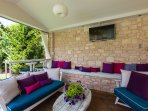 The outdoor sitting area is equipped with sofas and flat-screen TV!
