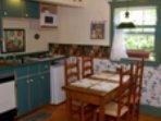 Kitchen has dishwasher, coffee maker, pots/pans, dishes, tea, coffee, sugar, small fridge, table/ 4