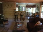 Creekside Cabin living room looking into kitchen.  Great bar to keep chef company while cooking!