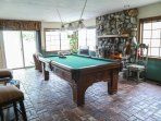Family room with brick floor, river rock fireplace and pool table