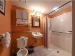 2nd bathroom with accessibility features like wide door, level roll-in bath and support rails.