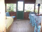 porch with daybed and dining table with view of lake