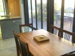 Dining table near kitchen showing bifold doors to outdoor area BBQ in right corner not shown.