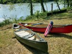 Two new canoes, with oars and life jackets, ready to push out into the river