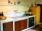Typically Tuscan stone built kitchen with marble sink, oven, hob and fridge