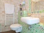 Bathroom with shower bath, basin, WC, heated towel rail, guest towels and shampoo