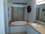 Master bathroom with large relaxing bathtub.  Shower and toilet are enclosed to the left.