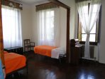 Spacious room with 3 beds, and 3 windows, wooden floors