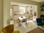 Kitchen leading through from living room. 6-8 chairs can fit around table, more chairs available