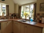 Kitchen with fridge freezer, dishwasher, microwave and small oven and hob  Aga for the winter months
