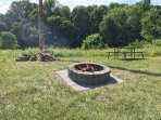 Fire pit, table, firewood, and grill on pole