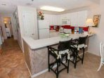 Fully equipped kitchen with two barstools