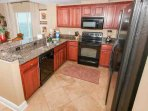 Fully equipped kitchen with granite counters and black appliances