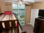 Guest room with TV, ceiling fan and lagoon view