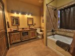 Master bathroom with custom tile and barnwood vainity including jacuzzi tub