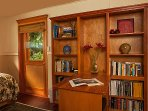 built-in shelving and desk in master bedroom, with door to covered deck & corner of twin bed visible