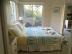 Large queen size bed has some privacy from the sitting area and opens to the balcony.