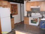 Another picture of the kitchen with refrigerator and stove