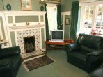 The smaller sitting room has a television and loads of comfy seats