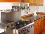 The kitchen has a gas range with double oven and an electric cooker, ideal for cooking for a large group