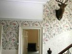 The centre of the house is the hall and staircase with beautiful wallpaper and sweeping stairs