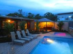 Lounge chairs and pool in the evening glow. Come stay at your Hideaway in La Fortuna!
