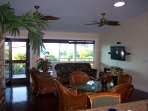 Open living space with comfortable hawaiian rattan furnishings. The door leads out to the lanai.