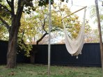 Our hammock chair is perfect for a nap. Backyard shown with autumn foliage.