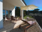 Terrace with dining table and deck chairs (OLIVI)