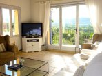 Main living area with panoramic views, sofa seating for 10. Sky TV, fireplace.