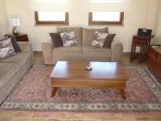 The living area has ample seating for six, along with 2 nests of tables, coffee table and TV cabinet