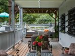 Walk out huge covered back deck has a hanging chair, couch area, picnic table, BBQ and hammock