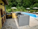 The outdoor kitchen with pizza oven, gas & wood BBQ, fridge, sink, and bar with stools.