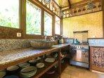 Villa: Kitchen with granite counter top, river stone sink and carved Myanmar cupboard door.