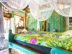 Villa: Carved bed, hand batik bed spread, antique Javanese carved walls.