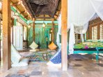"""Villa: Indonesian marble floors.  The ceiling is supported by a traditional carved teak """"soko""""."""